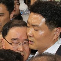 Взрыв возмущения: Премьера-министра Южной Кореи Чон Хун-Вон защищают его телохранители от бутылки воды, брошенной из рассерженной толпы из-за пассажиров, погибших на пароме Sewol. Фото: Йонхап / Yonhap.